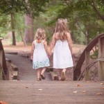 6355784045463228681049316941_Two-sisters-holding-hands-across-a-bridge-in-the-woods-1(pp_w856_h571).imgopt1000x70